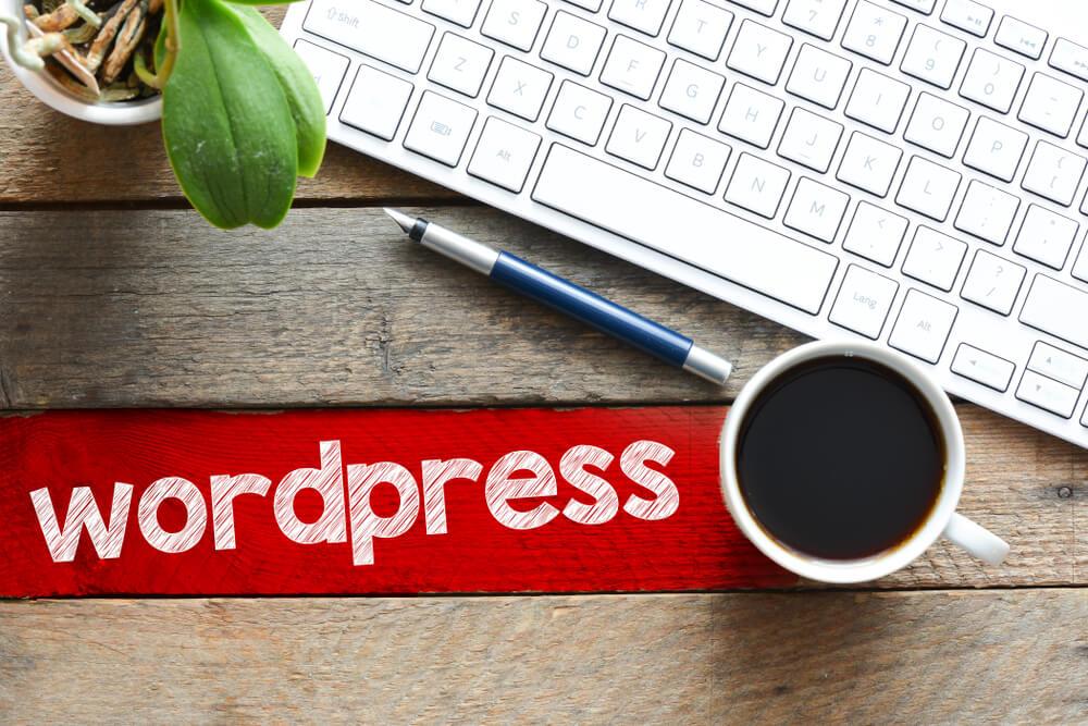 mesa de escritorio com teclado de computador, xicara de cafe e caneta com a palavra wordpress ao lado