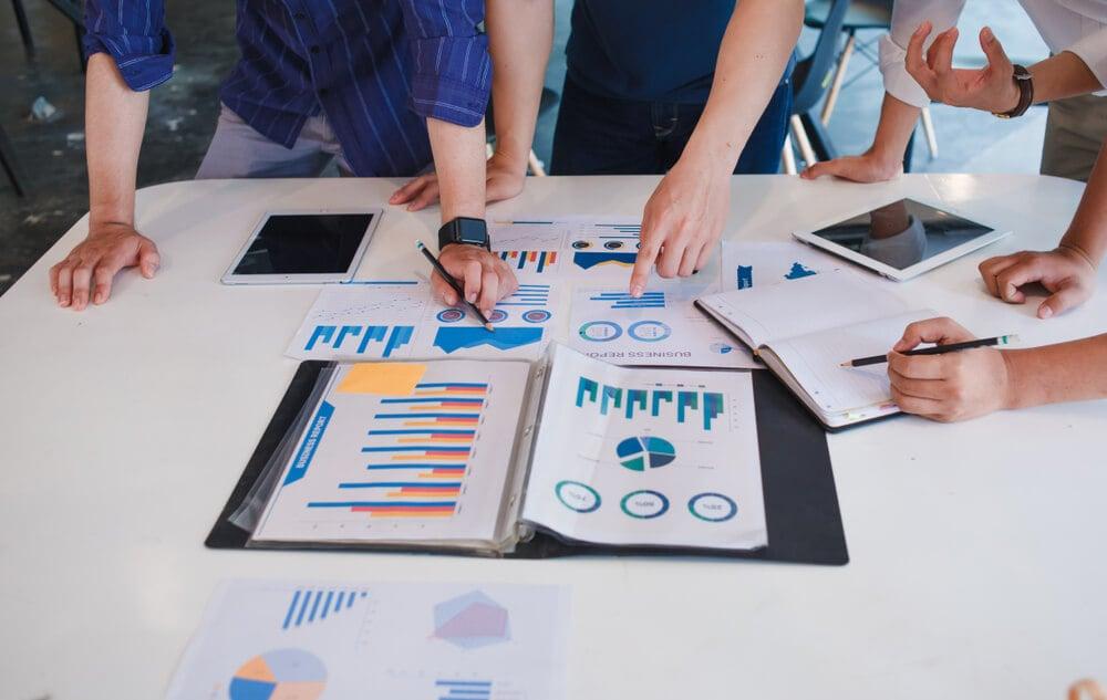 mesa executiva com diferentes profissionais efetuando pesquisa de mercado