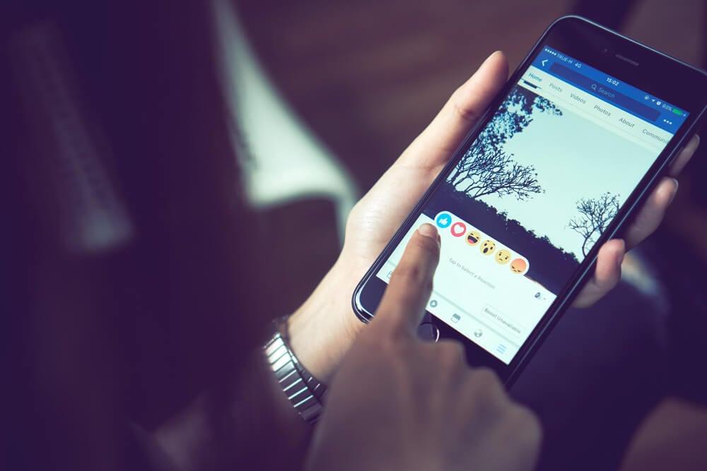 mulher com smartphone em maos com reaçoes de publicaçao do aplicativo facebook em tela