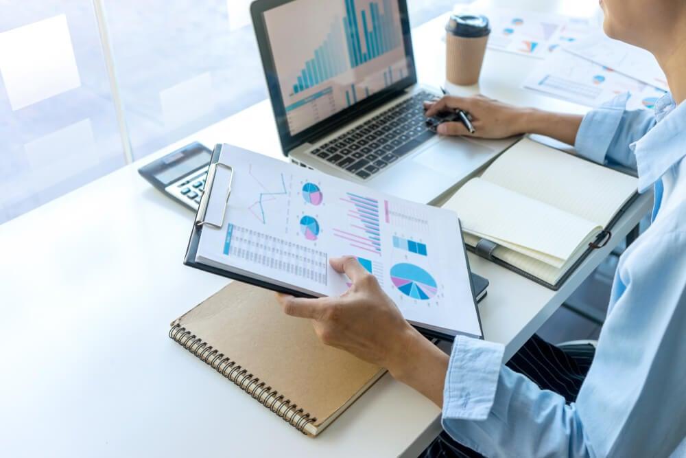 mulher em frente a laptop segurando tabela de graficos com cadernos, blocos de notas e calculadora em mesa