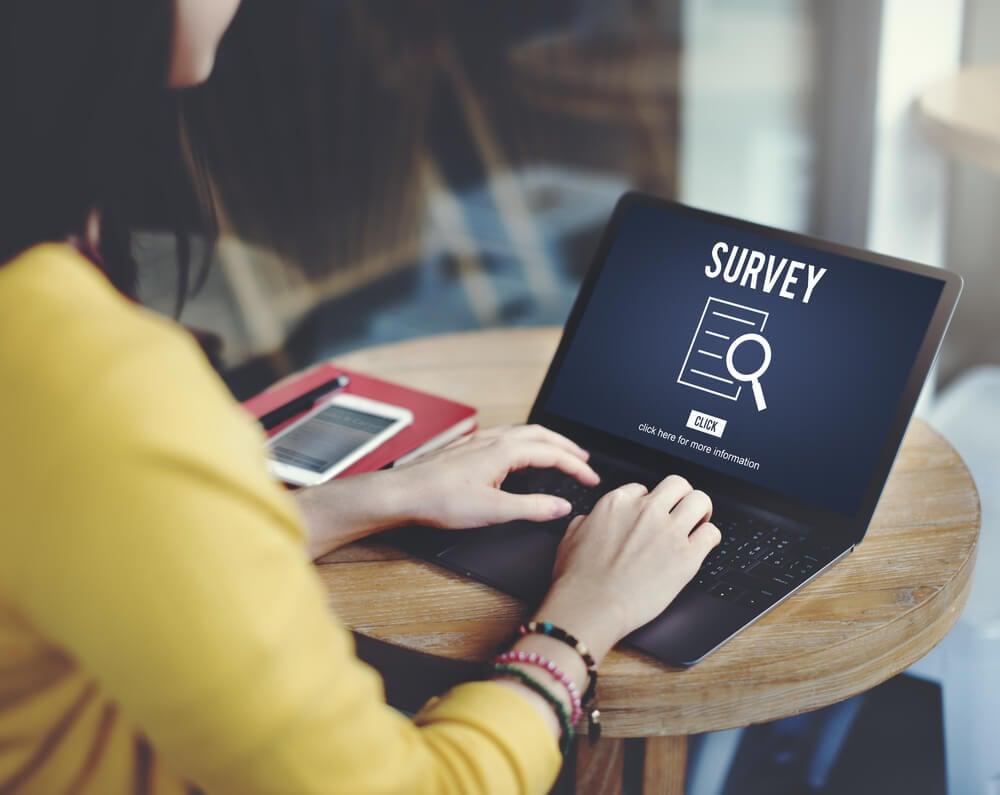 mulher em mesa com caderno e smartphone ao lado teclando em laptop com a palavra survey em tela