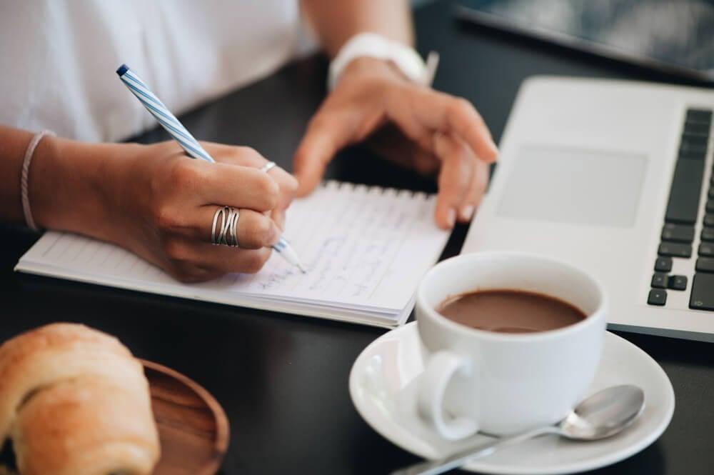mulher escrevendo em bloco de notas com xicara de cafe e laptop ao lado