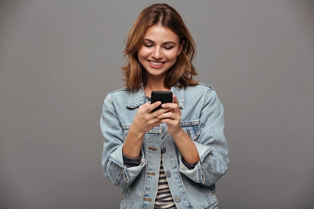 mulher segurando smartphone e sorrindo ao olhar para tela do mesmo em fundo cinza