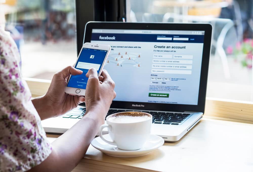 mulher segurando smartphone em frente a laptop com xicara de cafe ao lado e aplicativo facebook em tela