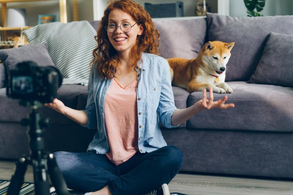 mulher sentada em frente a camera em tripe criando conteudo para canal no youtube
