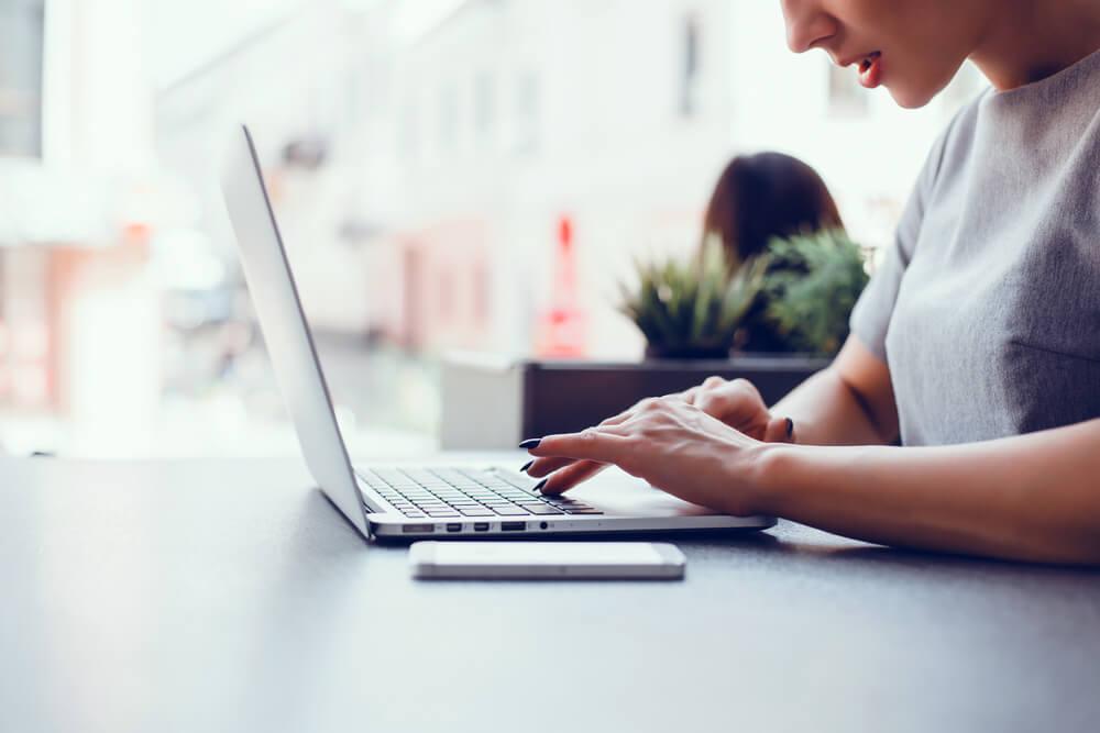 mulher usando laptop sob mesa com smartphone ao lado