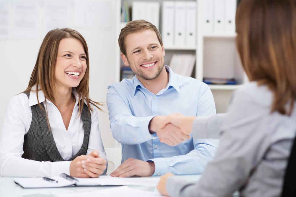 profissional apertando mao de clientes com expressao sorridente em escritorio simbolizando a satisfaçao do cliente
