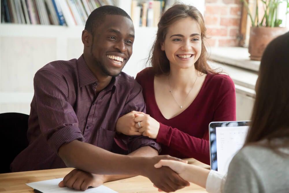 profissional apertando mao de clientes com expressao sorridente em escritorio