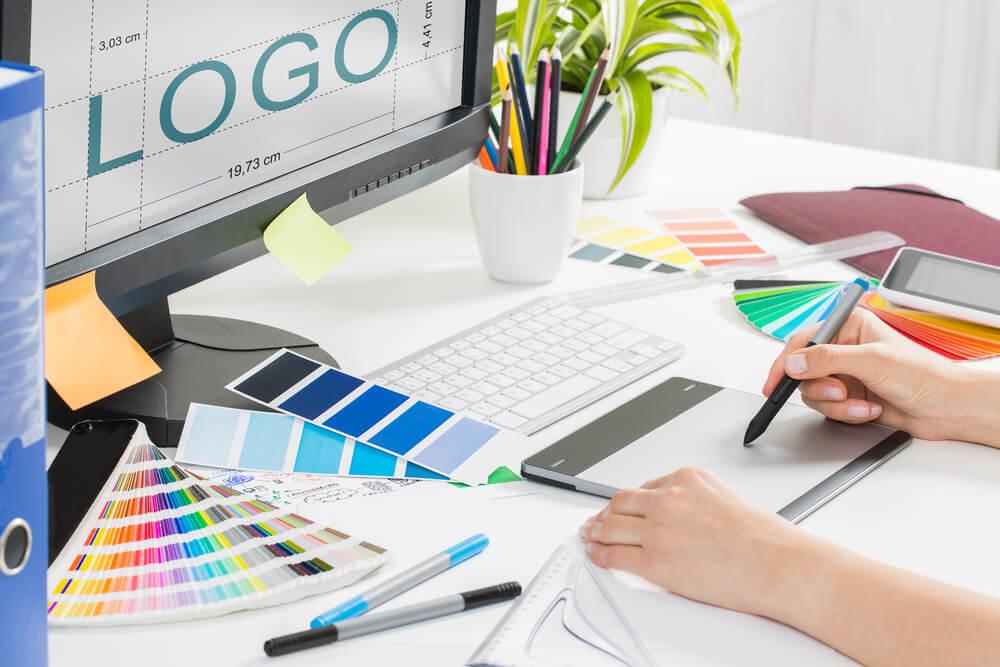 profissional em design escrevendo em bloco de notas em frente a computador com a palavra logo em tela em mesa de escritorio