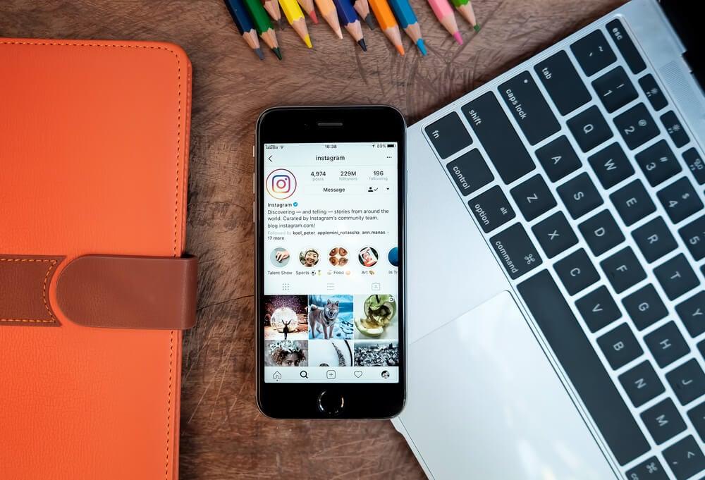 smartphone sob teclado de laptop em mesa com perfil do aplicativo instagram em tela