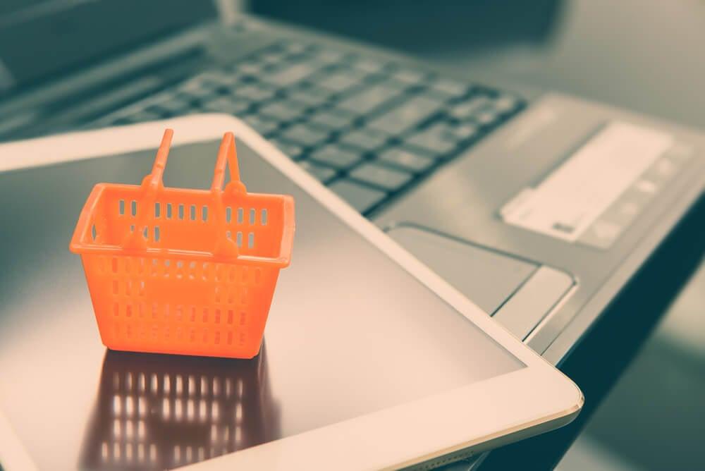 tablet em teclado de laptop com mini cesta de compras sob o mesmo