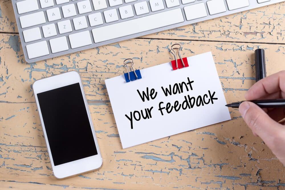 teclado e smartphone em mesa ao lado de nota com a frase we want your feedback