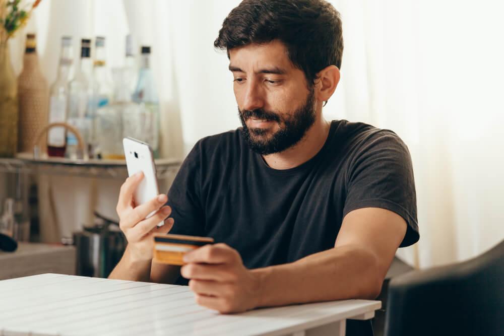 cliente de e-commerce segurando smartphone e cartão de crédito