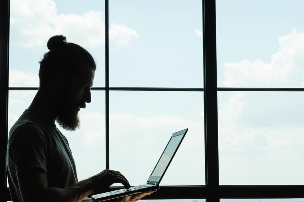 digital influencer segurando laptop em frente a janela