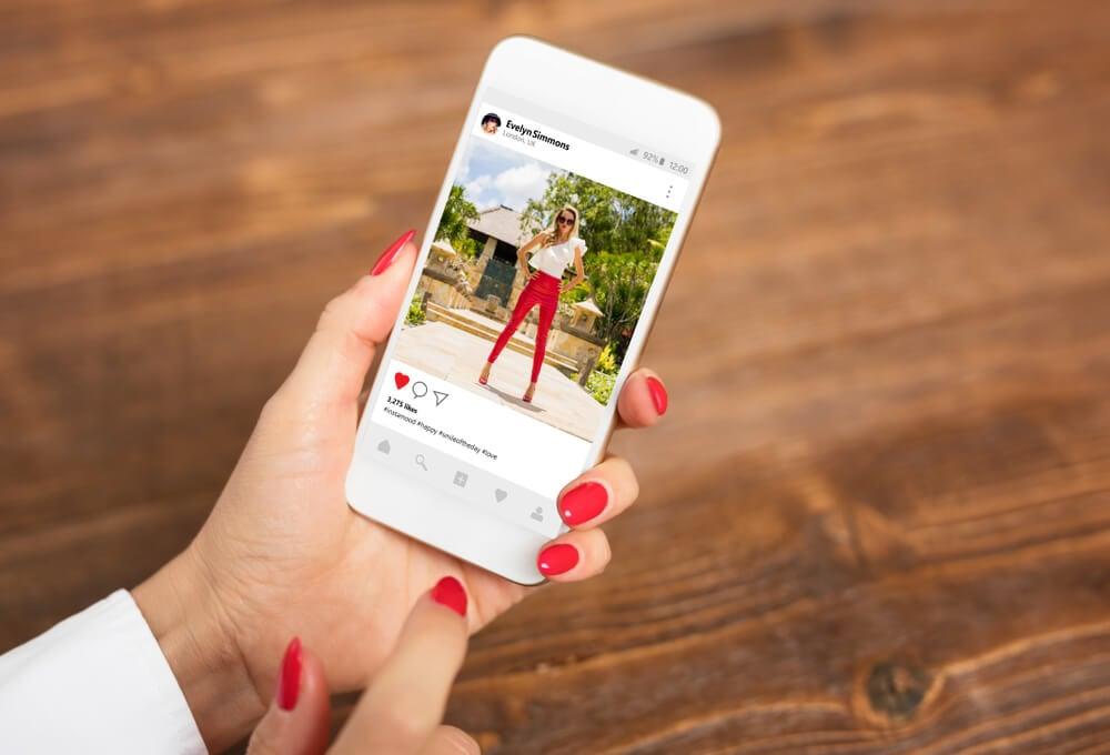 maos femininas segurando smartphone com publicaçao em feed em tela