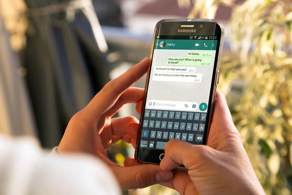 maos segurando smartphone com conversa do aplicativo whatsapp em tela
