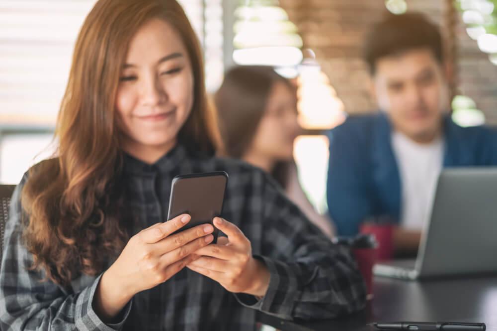 mulher em local publico utilizando smartphone