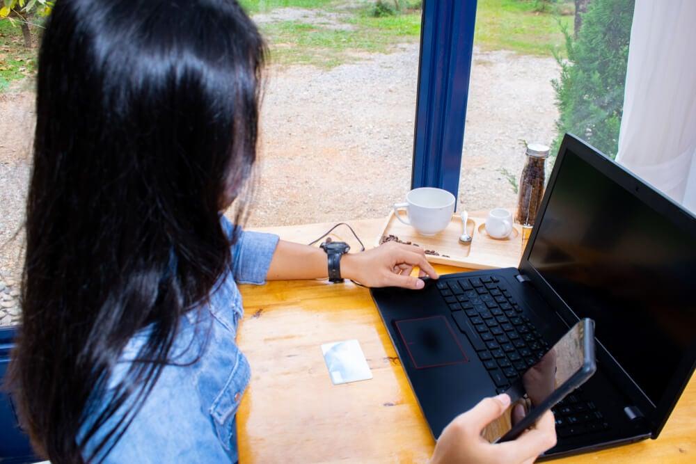 mulher profissional  trabalhando em frrente a laptop e acessando smartphone