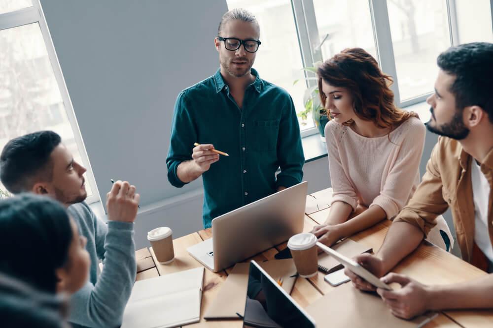 equipe reunida em mesa analisando plano de marketing pessoal
