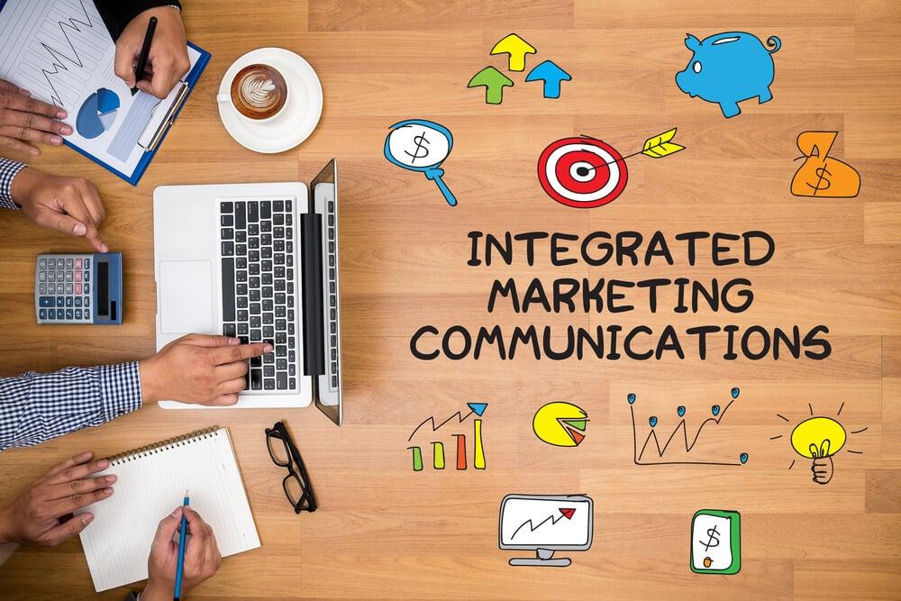 visão superior de mesa de trabalho com título comunicação integrada de marketing