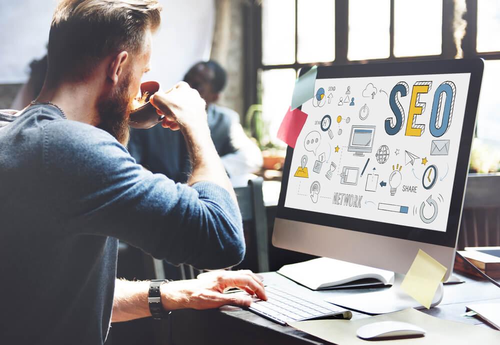analista de SEO em escritório segurando xícara de café e teclando em computador com a palavra SEO em tela