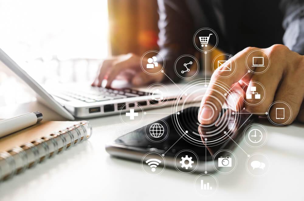consultor com mao direita apoiada em teclado de laptop e mao esquerda em tela de smartphone com ilustraçao de simbolos de marketing digital em destaque