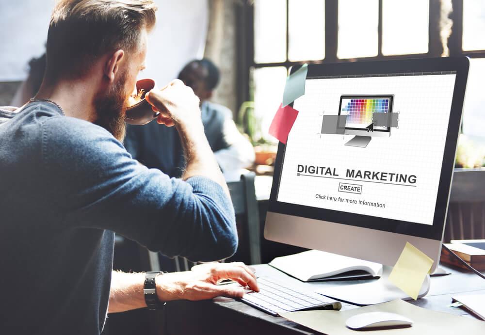 consultor em escritório com xicara de cafe em mao em frente a computador com as palavras digital marketing em tela