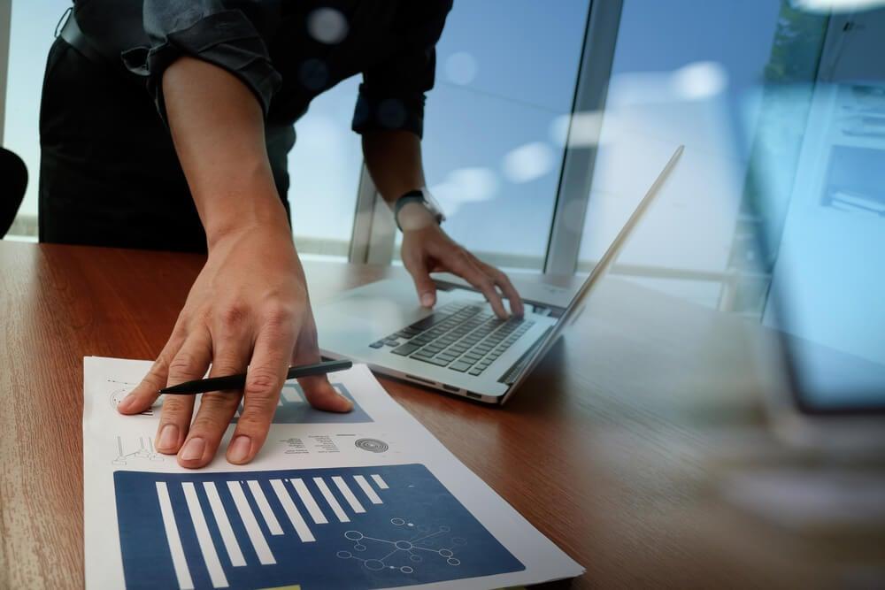 consultor em frente a mesa executiva segurando caneta e papel com graficos e com os demod em teclado de laptop