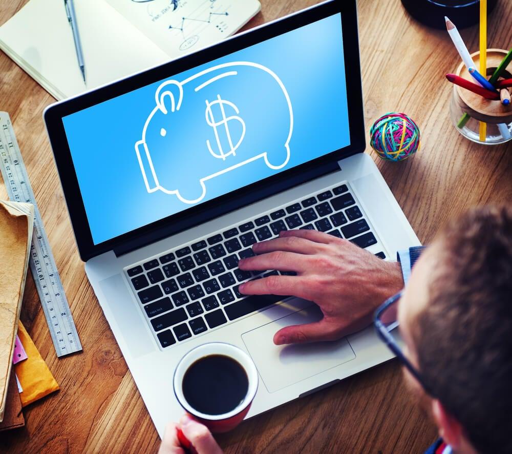 consultor segurando xicara de cafe em frente a laptop com ilustraçao de cofre de porco em tela