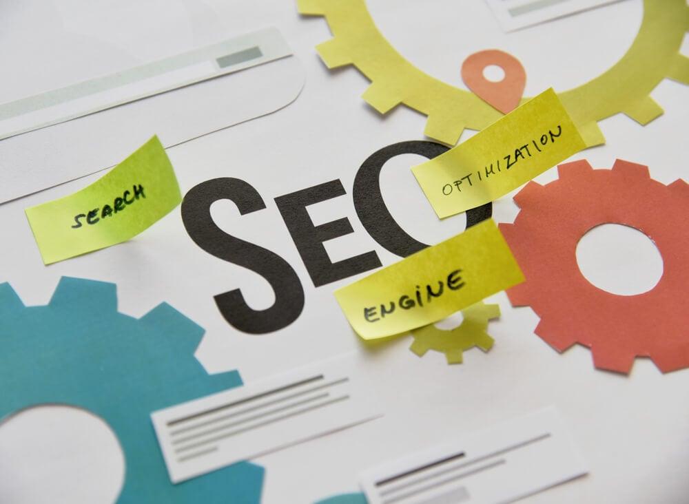 ilustraçao de engrenagens com a palavra SEO em destaque e post its com as palavras search, optimization e engine