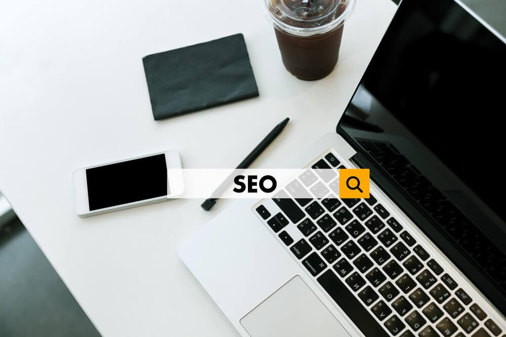 laptop em mesa com smartphone, caneta, bloco de notas e suco ao lado, com a palavra SEO em destaque