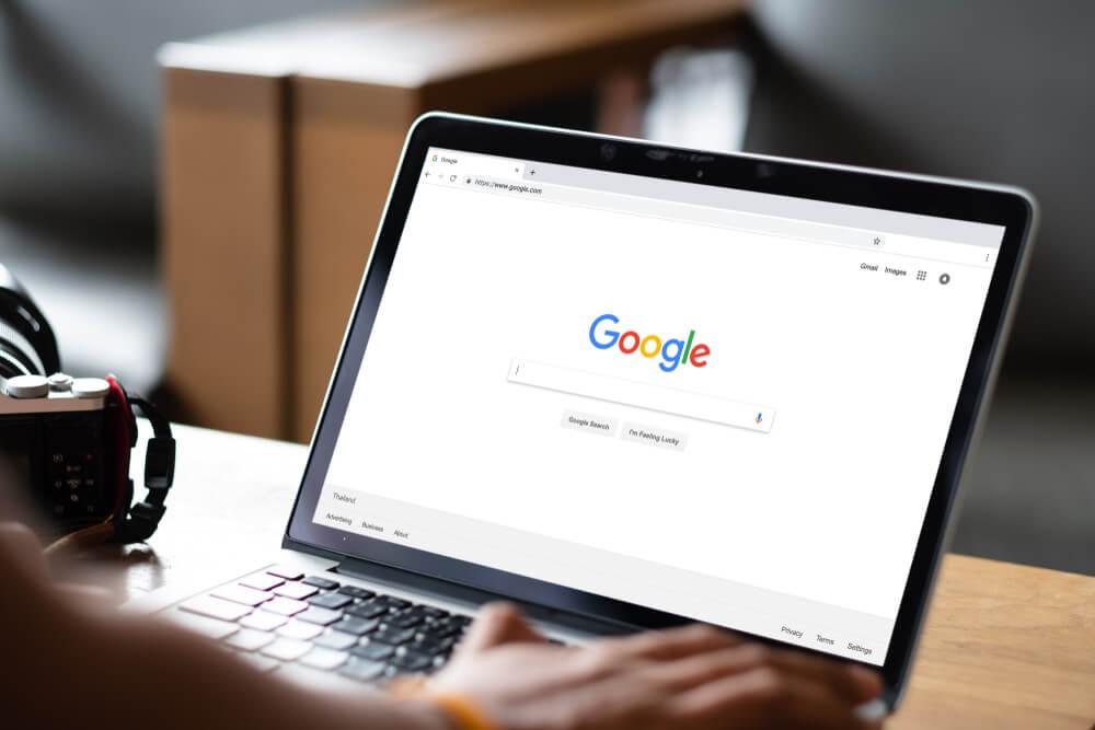 mão masculina em teclado de laptop com pagina do Google em tela