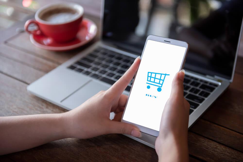 maos femininas segurando smartphone com carrinho de compras em tela simbolizando o e-commerce