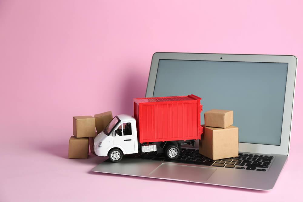 mini caminhão e caixas em cima de laptop em fundo rosa simbolizando o e-commerce