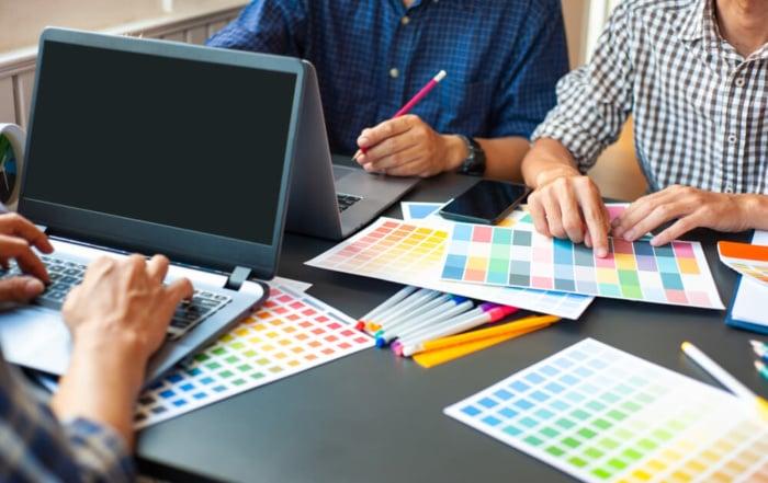 diversas paletas de cores impressas com a mão de homens manuseando além de outra mão masculina mexendo em um notbook
