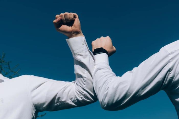 dois braços masculinos se cruzando sobre um céu azul