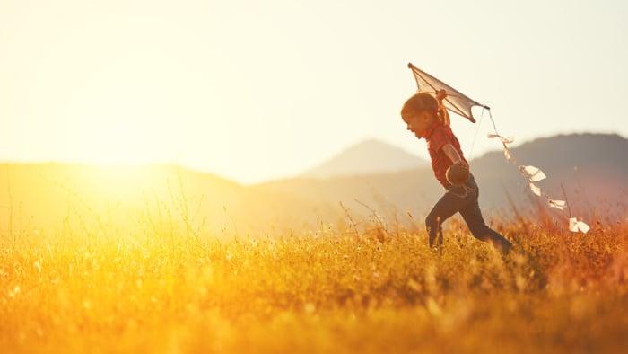 criança correndo com pipa na mão sobre um gramado